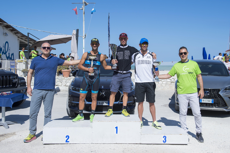 Il podio della prima edizione del Conero Wild Triathlon Portonovo. Premiano l'Assessore Andrea Guidotti (a destra) e Davide Tucci, presidente di Conero Wellness (a sinistra).